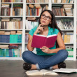 Stock Photo: Thoughtful student. Beautiful young woman holding book and looki