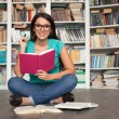 Student in library. Cheerful young woman holding book and lookin — Stock Photo