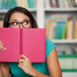 Scared student. Shocked young woman looking out of a book and lo — Stock Photo