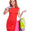Woman with credit card. Cheerful young woman in red dress holding shopping bags and credit card while standing isolated on white — Stock Photo