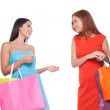 Girls shopping. Two cheerful young women holding shopping bags and talking to each other — Stock Photo