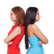 Girls confrontation. Two beautiful young woman standing back to back and keeping arms crossed while isolated on white — Stock Photo