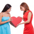 It is mine! Two young angry women holding one heart shape and looking at each other while standing isolated on white — Стоковая фотография