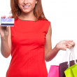 Easy shopping. Cheerful young woman in red dress holding shopping bags and credit card while standing isolated on white — Stock Photo