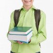 Boy carrying a stack of books and smiling — Stock Photo