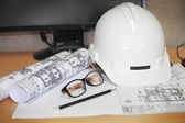 File of safety helmet and architect plant on wood table — Stock Photo
