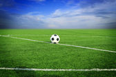 Soccer ball on soccer field with sun set — Stock Photo
