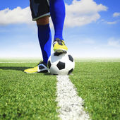 Soccer ball with feet player on the football field — Stockfoto