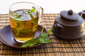 Green tea and leaves of mint in a glass cup — Stockfoto