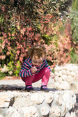 Cute little baby girl sitting under the olive tree — Stock Photo