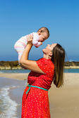 Mother and cute little baby girl on the beach — Stock Photo