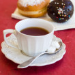 A cup of tea with fresh chocolate donuts — Stock Photo
