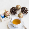 Stock Photo: Christmas composition with cup of tea, balls and bumps