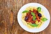 Pasta with tomato souse, olives and basil — Stock Photo