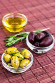 Plates of green olives, black olives and olive oil on bamboo nap — Stock Photo