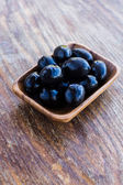 Plate of black olives on wooden surface — Foto de Stock