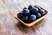 Plate of black olives on wooden surface — Stockfoto