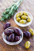 Plate of green and black olives on wooden surface — Stockfoto