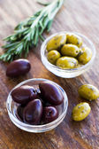 Plate of green and black olives on wooden surface — Stock Photo