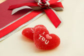 Two red sweet hearts on a gift box — Stock Photo