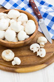 Fresh mushrooms in a cup on a wooden surface — Stock Photo