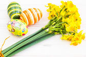 Easter eggs with yellow daffodils — Stock Photo