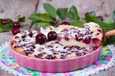 Slice of clafoutis with cherry in ceramic form — Stock Photo