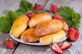Fresh baked pasties with strawberries on plate close-up — Stock Photo