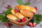 Fresh baked pasties with strawberries in a basket close-up — Stock Photo