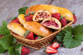 Slice of fresh baked pasties with strawberries in a basket close-up — Stock Photo