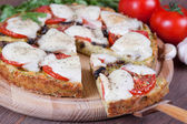 Slice of zucchini pizza and cheese on a wooden board, close-up — Stock Photo
