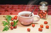 Still life with cup of fresh tea and rose hips on the wooden table — Foto Stock