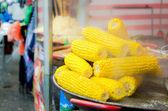 Boiled fresh yellow corn cobs on pan on market — Stock Photo