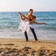 Young couple practicing a dance scene at the beach. — Stock Photo #35741653