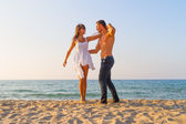 Oung couple teasing one another at the beach — Stock Photo