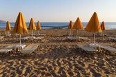 Beach sun beds and shade unbrellas. — Stock Photo