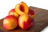 Delicious ripe juicy nectarines on brown wood isolated on white — Stock Photo