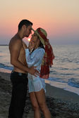 Happy young couple tenderly embracing and kissing at the beach at dusk. — Stock Photo