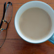 Stock Photo: Coffee cup and glasses on red wood