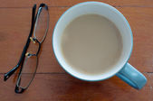 Coffee cup and glasses on red wood — Stockfoto