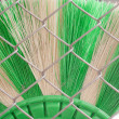 Green and white broom and wire mesh — Stock Photo