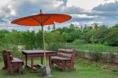 Borwn chairs and orange umbrella in garden with cloud — Stock Photo