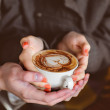 Four hands wrapped around a cup of coffee — Stock Photo #35979611