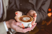 Four hands wrapped around a cup of coffee — Stock Photo