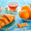 Cup of tea, croissant and mandarines — Stock Photo