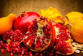 Pumpkin and pomegranate on fabric background — Stock Photo