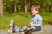 Smiling boy in rollers sits on walkway at park — Stock Photo