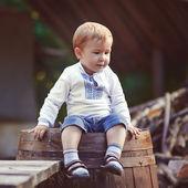 Liten pojke sitter på fat i byn — Stockfoto