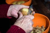 Hands peeling potato — Stock Photo