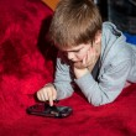 Tween boy with psp sitting — Stock Photo